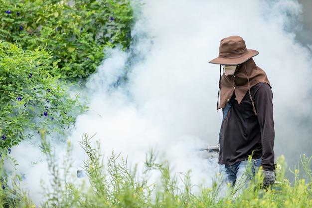 Человек запотевает химикат для устранения комаров на улице