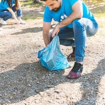 Man folding trash in garbage bag