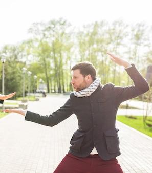 Человек дурачиться в позе самурая на открытом воздухе.