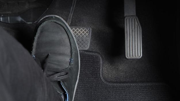 자동차나 차량 내부의 남자 발과 가속기 및 브레이크 페달과 검은색으로 된 복사 공간