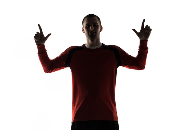 Человек футбол футболист силуэт в студии, изолированные на белом показывает знак