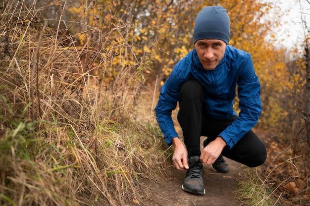 Uomo nella foresta che si allaccia i lacci delle scarpe