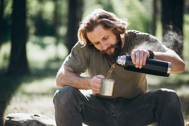 Man in forest with tea by fire
