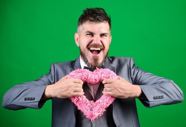 男のフォーマルなスーツは、バレンタインデーの緑の背景を祝います。周りに愛を広めます。恋に幸せ。いちゃつくロマンチックなマッチョ。幸せなバレンタインデー。ヒップスターはハートシンボルの愛を保持します。ロマンチックな驚き。