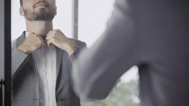 Man in formal suit getting dress in dressing room.