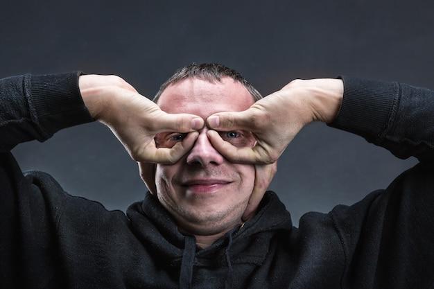 Человек, формирующий очки руками над серым