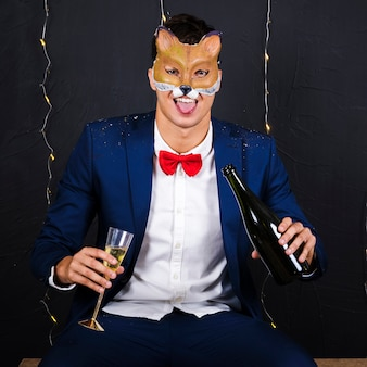 Man in fox mask holding glass and bottle of champagne
