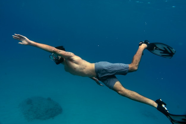 Man freediving with flippers underwater