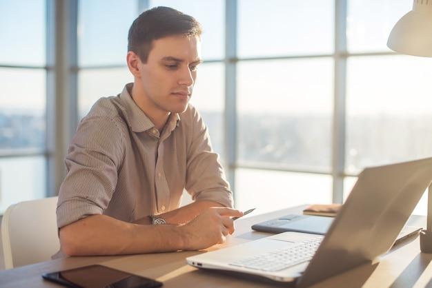 Человек фрилансер бизнесмен, работающий на портативном компьютере в офисе.