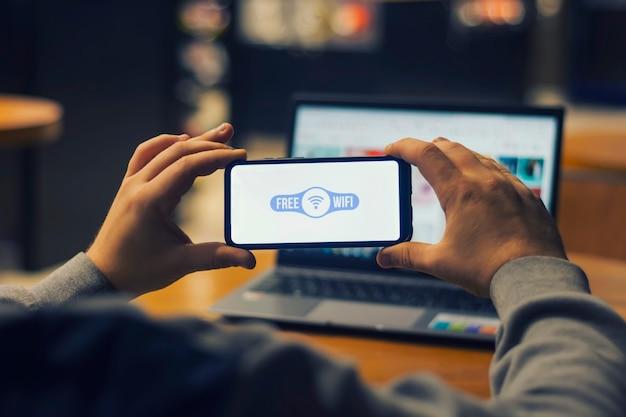 男のフリーランサーは、ラップトップの背景に彼の手で無料インターネットを備えたスマートフォンを持っています。
