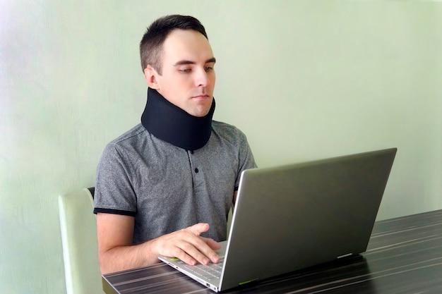 自宅で仕事をしている頸部カラーネックブレースの男性フリーランサー。プロテーゼのネックサポート。頸椎の骨折。首の痛みの治療。