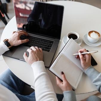 Мужчина-фрилансер печатает на ноутбуке, сидя за столом рядом с девушкой-менеджером, которая делает заметки в блокноте