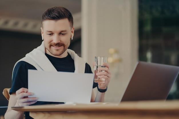 Человек-фрилансер, глядя на документ перед ноутбуком, сидя в домашнем офисе за своим рабочим столом, держа стакан воды и используя наушники, молодой бизнесмен в повседневной одежде работает удаленно из дома