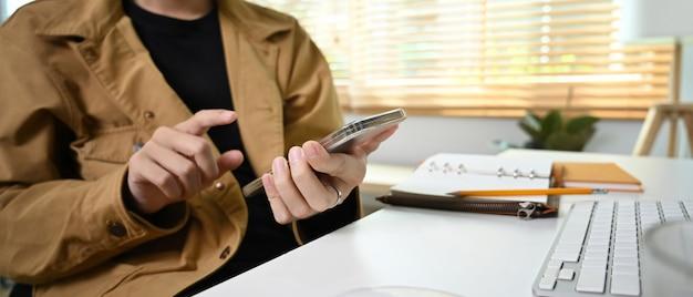 Фрилансер человек с помощью смартфона, сидя в гостиной.