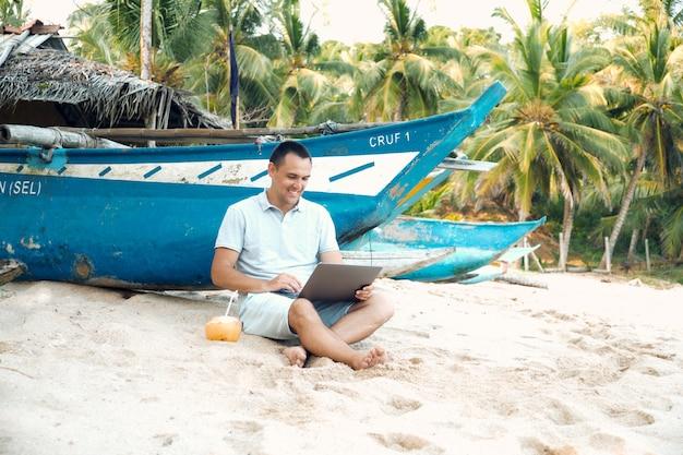 Man freelancer work by laptop sit on ocean beach