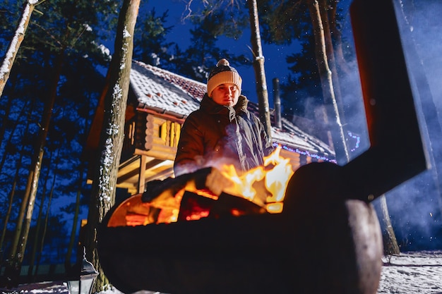 A man fries grilled meat against the cottage in the evening and in the smoke