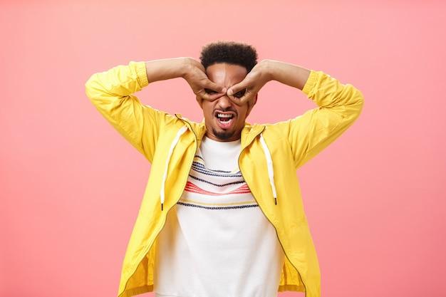 子供の頃から夢見ていた男がスーパーヒーローになります。ピンクの壁の上の黄色いジャケットに立っている目の上の手からマスクを作る未熟な演技の幼稚な遊び心のあるアフリカ系アメリカ人の若い男