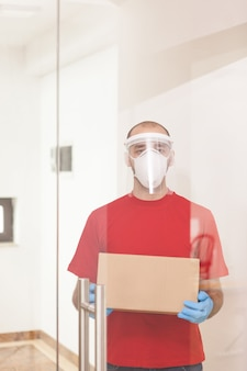 Man from delivery service carrying a box wearing protection mask.