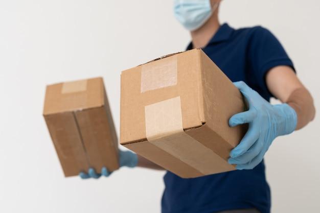 Человек из службы доставки в футболке, в защитной маске и перчатках дает заказ на еду и держит коробки на белом фоне.