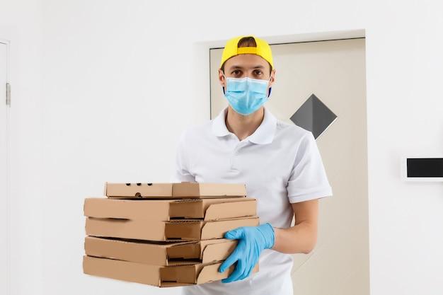 配達サービスの男性、tシャツ、保護マスク、手袋を着用して食品を注文し、白い背景の上にピザの箱を持っています。