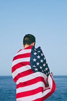Man from behind wrapped in american flag