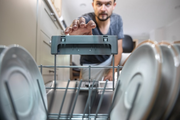 A man in front of an open dishwasher takes out clean dishes after washing