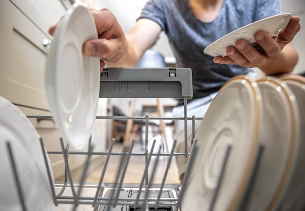 A man in front of an open dishwasher takes out clean dishes after washing.