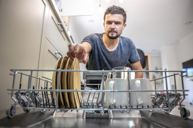 A man in front of an open dishwasher takes out or puts down dishes.