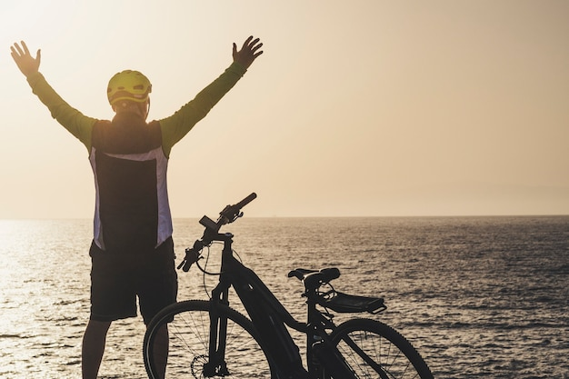 Man in front of sea with arms up looking the horizont at the sunset with his bike - freedom lifestyle concept and rider senior