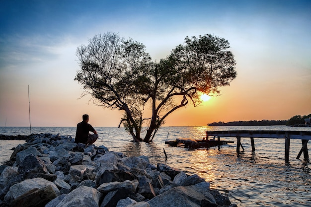 Man in frustrated depression sitting alone looking at tree