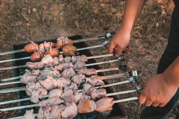 Man frying shish kebab on the grill. hands closeup outdoors