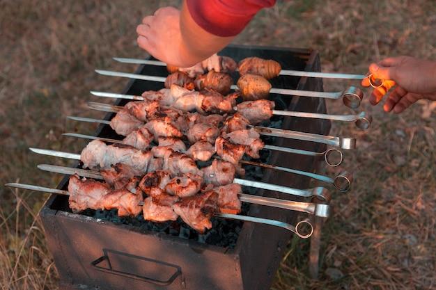 Man frying shish kebab on the grill. hands closeup outdoors.