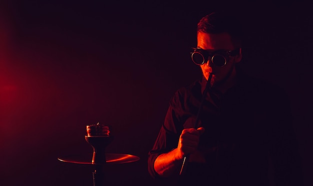 Man in futuristic glasses smokes a hookah in a bar with red neon lights
