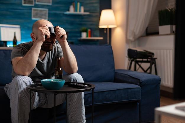 Геймер человек играет в спортивные видеоигры с контроллером, сидя на диване в гостиной