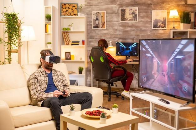 Мужчина-геймер, использующий гарнитуру vr, чтобы играть в видеоигры в гостиной поздно ночью