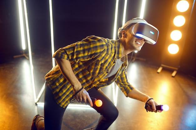 Человек, играющий в гарнитуре виртуальной реальности и геймпаде в светящемся кубе