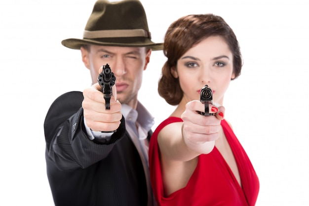 Man gangster and sexy spy woman with guns.