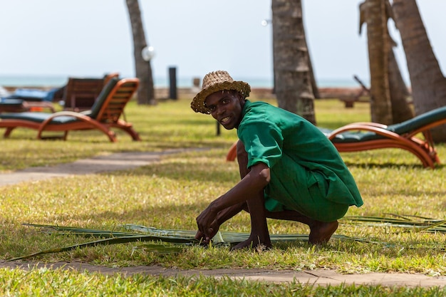 Man gardener hotel worker, a black-skinned man works to the gardeners i