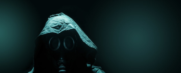 Man in the gas mask in the hood, on the dark background, survival soldier after apocalypse