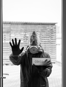Man in a gas mask, a respirator shows through the glass door a stop sign with his palm and a card with the letters covid-19 coronavirus in a pandemic, covid-19 focus on the card