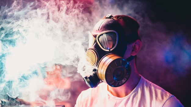 Man in a gas mask smokes a hookah and breathes a cloud of tobacco smoke
