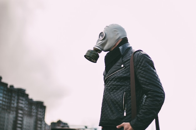 Man in a gas mask walking through a city parking lot