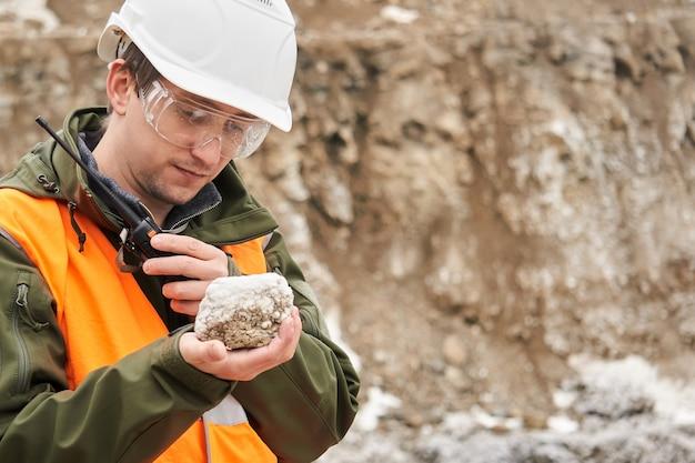 Геолог человек исследует образец минерала