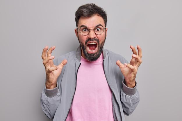 Мужчина жестикулирует сердито восклицает от раздражения не может стоять что-то возмущено выражение носит круглые очки куртка изолирован на сером