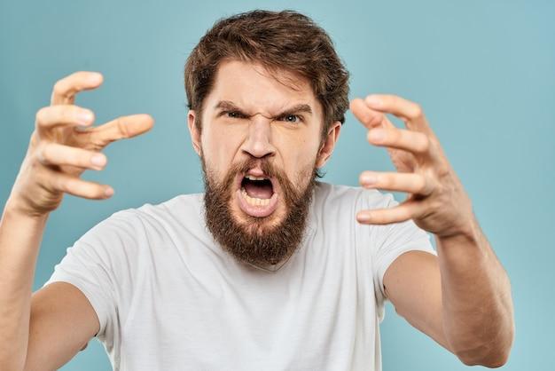 彼の手で男のジェスチャー感情不快感白いtシャツ青い背景