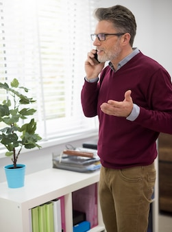 Man gesturing while talking on the phone