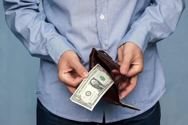 남자는 지갑에서 돈을 얻습니다. 1 달러와 가죽 지갑을 들고 손 클로즈업. 빈곤과 실업.