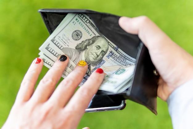 남자는 지갑에서 돈을 얻습니다. 그 남자는 녹색 배경에 급여를 다시 계산합니다. 남자 손톱의 아름다운 디자인.