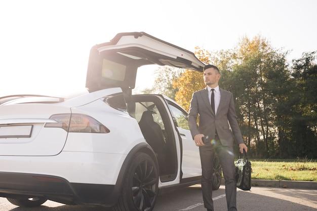 男は日中に駐車場で白いエグゼクティブカーから降りる