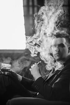 男はvapingから喜びを得ます。ニコチンタバコの健康的な代替品。たくさんの煙を吐き出し、リラックスして満足している。